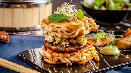 Pan-Asian cuisine concept. Ramen Chinese rice noodle burger, chicken and pork cutlet and salad, with wasabi sauce. Background image. Serving dishes with french fries. copy space