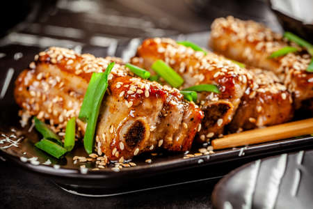 Asian food. Fried pork ribs in sweet and sour sauce with sesame seeds. Beautiful dish in a restaurant in a flat black plate. Background image. copy space Stok Fotoğraf