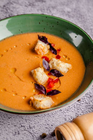 Spanish cuisine. Cold summer tomato soup gazpacho with croutons and basil.