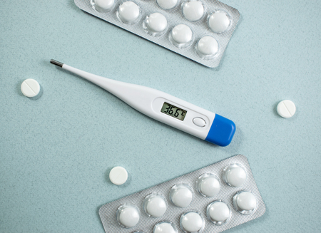 Medical background with multi-colored packs of pills. Ð¡oncept pharmacy, clinic, drugs, headache medicine. Image on illness, flu, treatment. Image of a thermometer with a normal temperature