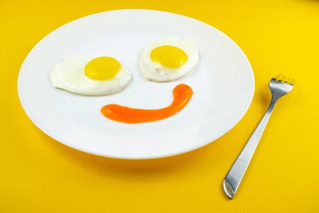 traditioneel ontbijt van twee gebakken eieren. Leuk gezicht van eten. Bord met eieren op een gele achtergrond. Concept afbeelding van ontbijt, gezond eten