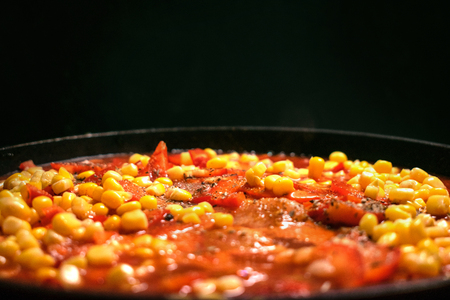 stewed vegetables, corn, tomatoes, sweet peppers, potatoes, miao in a pan on a dark background. Close up view. Stock Photo