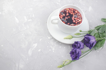 Mixture herbal floral tea with petals, dry berries and fruits. healthy drink. Hot fruit, healthy tea in a white mug.
