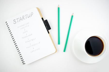 Minimalistic workplace concept, with a stationery, pen and business work records on a white background. Image of business plan, startup. Top view. Flat lay style