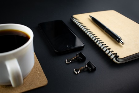 Minimalistic workplace concept, with a smartphone, pen and business work records on a dark background. Image of business plan, startup. Close up image Stockfoto