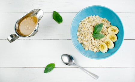 Plate with tasty oatmeal and banana slices on white wood background. Concept image of breakfast, healthy eating Stockfoto