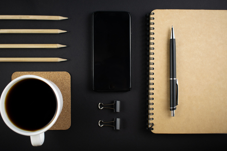 Minimalistic workplace concept, with a smartphone, pen and business work records on a dark background. Image of business plan, startup. Top view. Flat lay style