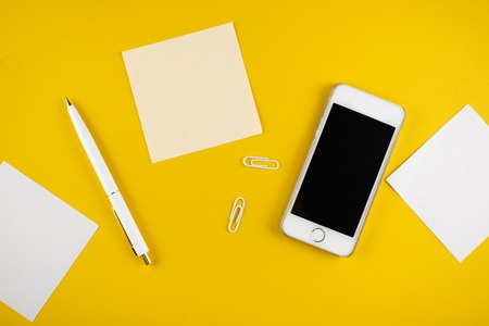 Minimalistic workplace concept, with a smartphone, pen and business work records on a dark background. Image digital, marketing, design agency. Top view. Flat lay style