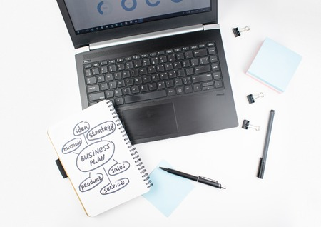 Minimalistic workplace concept, with a laptop, pen and business work records on a white background. Image of business plan, startup. Top view. Flat lay style