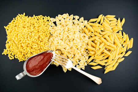 Various types of pasta on a dark background. Italian cuisine concept, food ingredients. Flat lay. Top view, copy space.