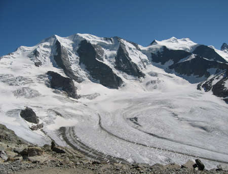 Unusual majestic peak Diavolezza in the snowy mountains of Switzerland. The emphasized coldness against a bright blue sky causes an exciting feeling of icy calm against a hot summer day. Side view