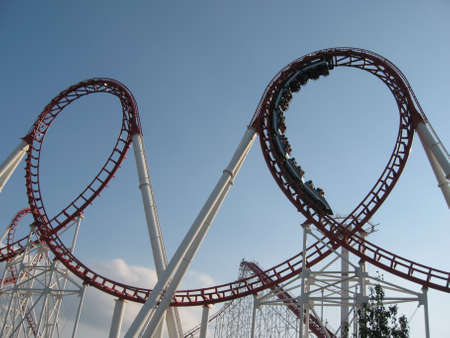 An exciting roller coaster ride at the amusement park. People in chairs fly at dizzying speeds. Bottom view