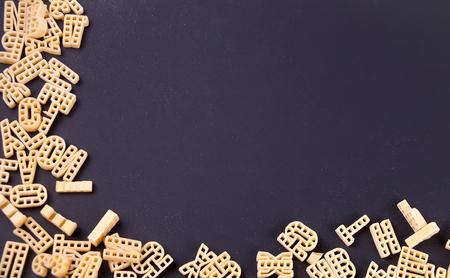 Raw macaroni alphabet frame on black background
