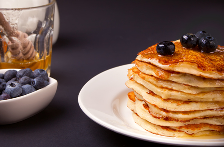 Pancakes with berries and honey on the black background Standard-Bild