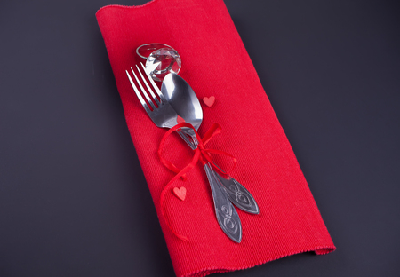 Festive table setting for Valentines Day. Spoon and fork on the red napkin.