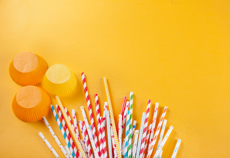 Drinking paper colorful straws for summer cocktails on yellow background. Top view.