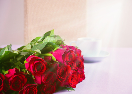 A cup of coffee and roses on the table