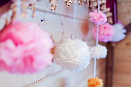 Festive decoration of paper pink and white pompons on a wall