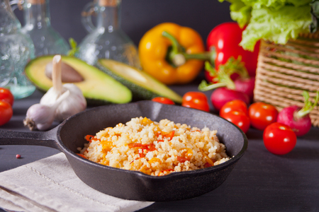 Homemade vegetarian couscous with tomatoes, carrots, pepper on a dark kitchen table with vegetables on the background