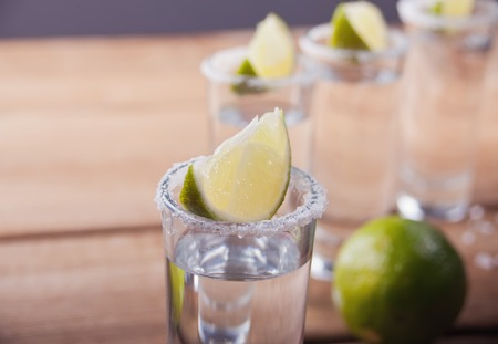 Tequila shot with lime and sea salt on wooden table, selective focus