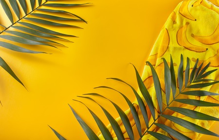 Tropical leaves and beach towel on yellow background. minimal concept. Flat lay. Zdjęcie Seryjne