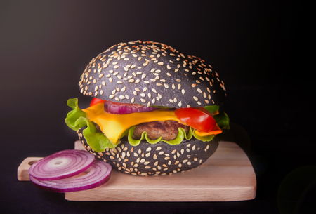 Homemade burger with vegetables and cutlet on the black background