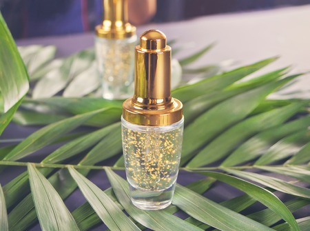 Shiny golden bottle with liquid and palm leaf . Stock Photo