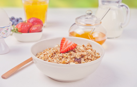 Muesli granola with strawberries, honey, milk on the white table.