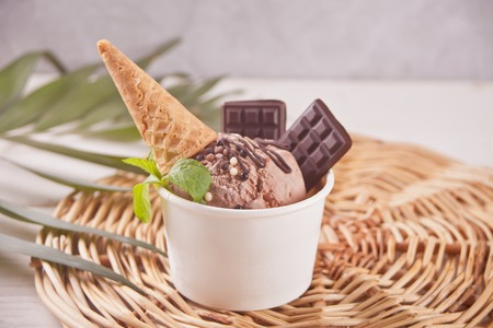 Paper bowl of chocolate ice cream and mint leaf with small waffle cone and chocolate