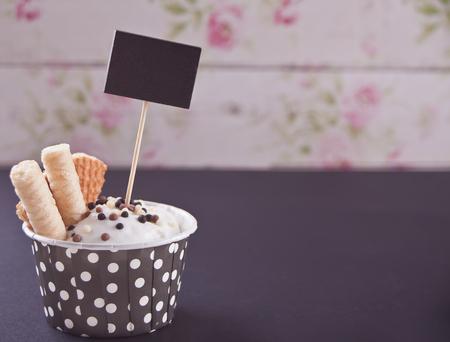 Paper polka dots bowl of vanilla ice cream with waffles on the black table. Copy space. Archivio Fotografico