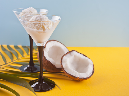 Coconut ice cream in a bowls on the yellow and blue background with palm leaf and coconut