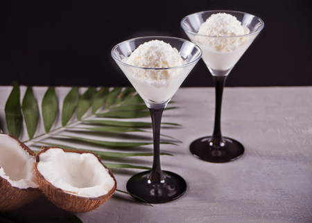 Coconut ice cream in a bowls on the gray background with palm leaf and coconut