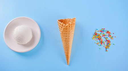 Vanilla ice cream on the white plate with waffle cones and colorful candies on the blue background 스톡 콘텐츠