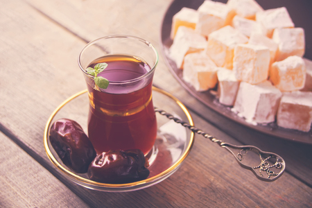 Turkish tea in traditional glass cup, date fruits and sweets on the wooden table. Oriental.