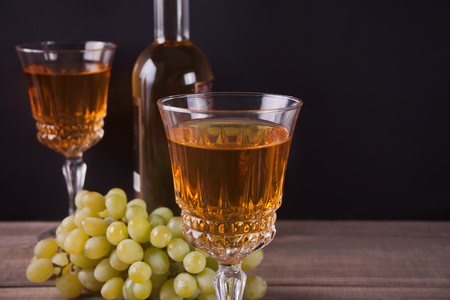 Two glasses of white wine, wine bottle and bunch of green grapes standing on a wooden table. Copy space.