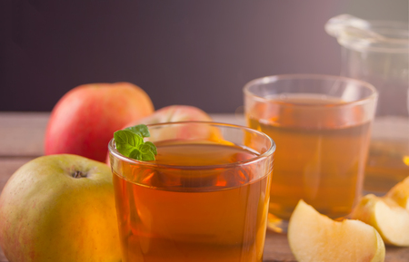 Apple juice and apples on wooden table. Selective focus. Close up. Imagens - 124444447