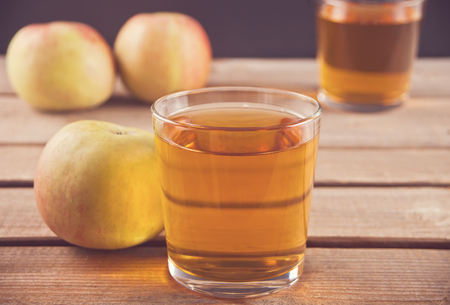 Apple juice and apples on wooden table. Selective focus. Close up. Imagens - 124444454