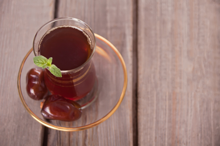 Turkish tea in traditional glass cup with sweet date fruits on the wooden table. Oriental. Copy space. Top view.
