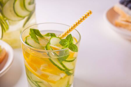 Refreshing summer drink with lemon, ginger, fresh cucumber and mint on the white background. The concept of healthy and dietary nutrition.