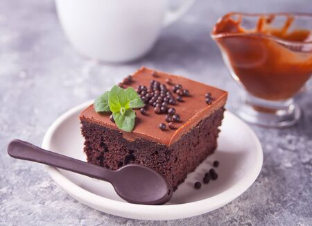 A piece of tasty homemade chocolate cake on the plate with icing, mint leaf and chocolate spoon on the gray background Stock fotó