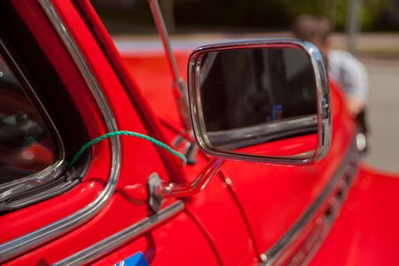 Red retro car rear view mirror. Close up.
