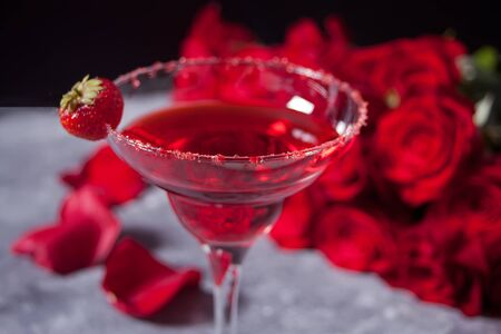 Red fresh exotic alcoholic cocktail in clear glass and red roses on the gray background