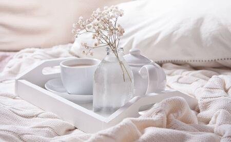 Nahaufnahme von Tasse Tee, Milch, Teekanne und Strauß weißer Blumen auf dem weißen Tablett im Bett. Romantischer Sommermorgen.