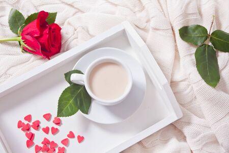 Nahaufnahme einer Tasse Tee mit roter Rose und kleinen Süßigkeitenherzen auf dem weißen Tablett auf dem Bett. Ansicht von oben.