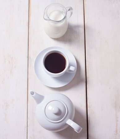 Cup of coffee, teapot and jug with milk in row over white wooden background. Flat lay, copy space.