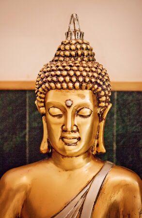 Close up yellow-gold statue Buddha in meditation
