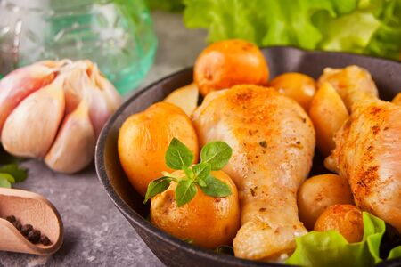Roasted chicken legs with spices and herbs on the black pan with vegetables on the background. Stock Photo - 129418299