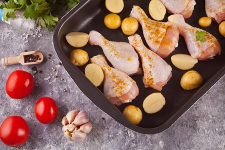 Roasted chicken legs with potato, spices and herbs on the black pan with vegetables on the background. Top view. Stock Photo - 129416416