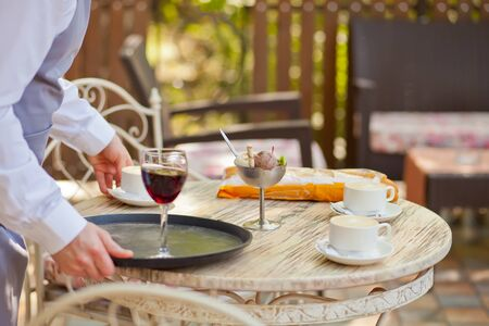 the waiter puts a glass of red wine on the table in a outdoor cafe