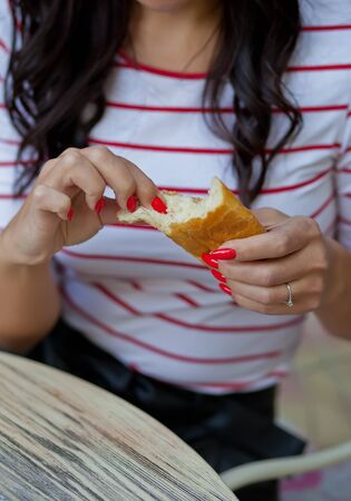Pretty brunette woman in a striped t-shirt sitting in outdoor cafe and eating bread.